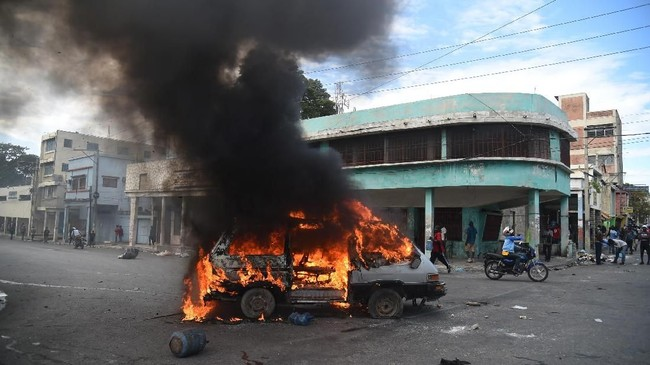 Di Port-au-Prince, beberapa kendaraan dibakar oleh pengunjuk rasa yang juga berusaha membakar sebuah pom bensin. (AFP Photo/Hector Retamal)
