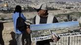 Penjaja oleh-oleh membuka peta Kota Lama Yerusalem yang menjadi barang jualannya.(AFP/THOMAS COEX)