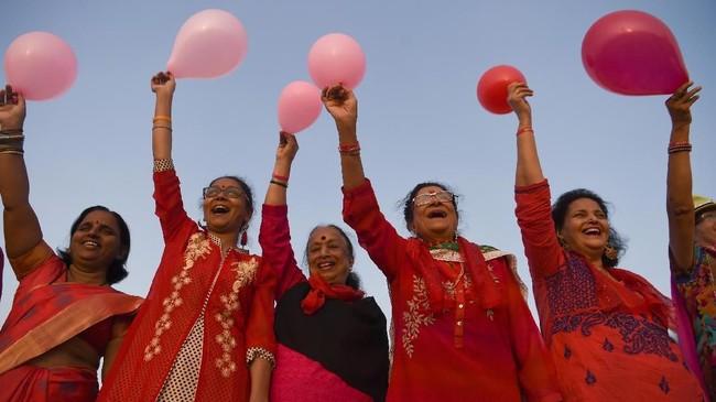 Di India, misalnya, Hari Kasih Sayang dirayakan oleh sebagian besar wanita lanjut usia. Mereka merayakannya dengan bermain balon berbentuk hati berwarna merah muda di pinggir Pantai Girgaon Chowpatty, Mumbai, India, Kamis (14/2). (Photo by Indranil MUKHERJEE/AFP)