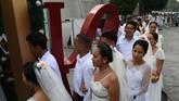 Di sudut lain Manila, sejumlah pasangan suami istri merayakan Hari Valentine dengan mengikuti agenda pernikahan masal pada Kamis (14/2). Sebanyak 200 pasangan tercatat mengambil bagian dalam gelaran tersebut. (Photo by TED ALJIBE/AFP)