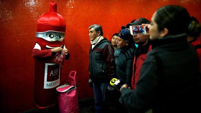 Sedangkan di Meksiko, seorang pria turut merayakan Valentine dengan membagikan kondom secara gratis. Dia mengenakan kostum yang merepresentasikan kondom di salah satu area publik di Meksiko pada Hari Kondom Internasional yang diperingati satu hari sebelum Hari Kasih Sayang, Rabu (13/2). (REUTERS/ Carlos Jasson)