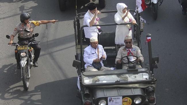 Gubernur Jawa Timur Khofifah Indar Parawansa (kanan) bersama Wakil Gubernur Jawa Timur Emil Elestianto Dardak (kedua kanan) menyapa warga dari atas mobil jip saat berparade di Jalan Wonokromo, Surabaya, 14Februari 2019. (ANTARA FOTO/Moch Asim)