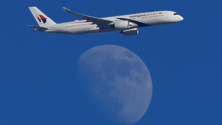 A Malaysian Airlines passenger aircraft is seen flying in front of the moon, over London, Britain, February 15, 2019. REUTERS/Toby Melville