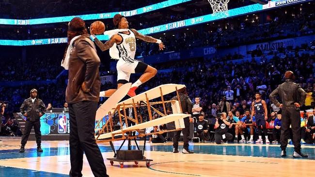 John Collins mempergunakan pesawat tiruan sebagai salah satu gimmick aksi slam dunk, selain juga topi dan syal khas penerbang zaman dulu. (Bob Donnan-USA TODAY Sports)