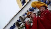 Seiring dengan dibawanya thangka ke lereng, sejumlah biksu memainkan sejumlah alat musik untuk mengiring doa. (REUTERS/Aly Song)