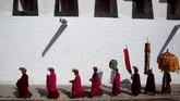 Ribuan biksu, penduduk, dan wisatawan di Tibet berkumpul kala sinar matahari pertama mengenai thangka Budha raksasa yang terbentang di lereng bukit. (REUTERS/Aly Song)