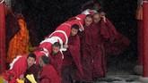 Para biksu bersama-sama menggotong thangka Budha raksasa ke lereng bukit sebrang biara. (REUTERS/Aly Song)