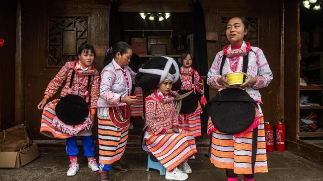 Mereka mengenakan kostum khusus, jaket bersulam mawar merah dengan motif geometris. (Photo by FRED DUFOUR / AFP)