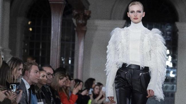 Detail feminin yang dikombinasikan dengan sentuhan maskulin serta bulu dan ruffles membuat gaya ini tampil elegan.(Photo by Niklas HALLEN / AFP)