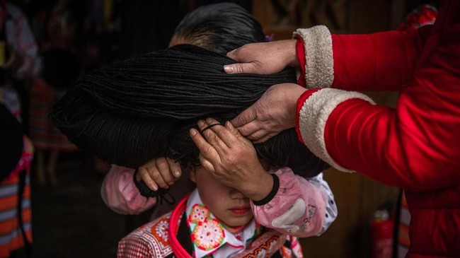 Gelungan itu terbuat dari wol, benang dan rambut leluhur mereka yang sudah meninggal. Ia kemudian dibungkus dengan kain warna putih dan tanduk binatang. (Photo by FRED DUFOUR / AFP)