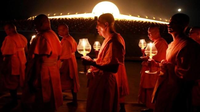 Mereka berjalan berjajar dan membawa semacam seserahan atau sesajen untuk Budha. (REUTERS/Soe Zeya Tun)