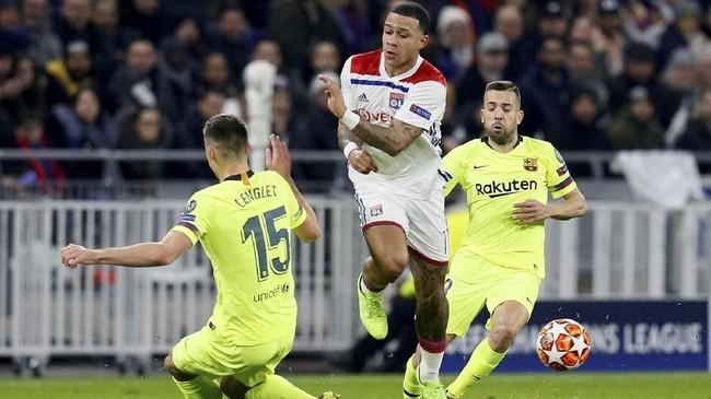 Pemain Lyon Memphis Depay berduel dengan dua pemain Barcelona Clement Lenglet dan Jordi Alba. Lyon sempat memberi perlawanan sengit di babak pertama. (REUTERS/Emmanuel Foudrot)