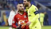 Penyerang Barcelona Lionel Messi memeluk kiper Lyon Anthony Lopes. Lopes melakukan sejumlah penyelamatan gemilang saat melawan Barcelona. (REUTERS/Emmanuel Foudrot)