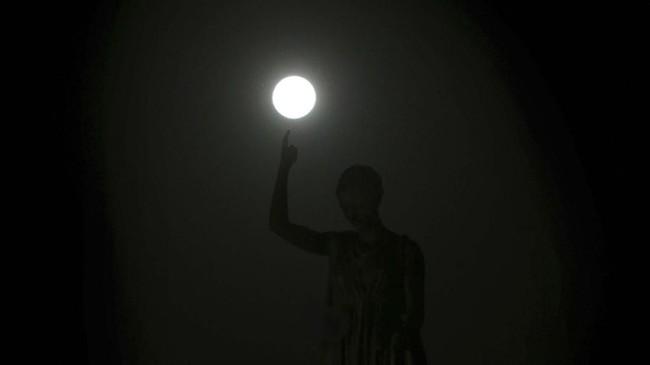 Supermoon terjadi akibat Bulan bergerak mengelilingi Bumi dalam bentuk elips bukan lingkaran. Tampak supermoon berada di atasLiberty Monument di Nicosia, Cyprus. (AP Photo/Petros Karadjias)