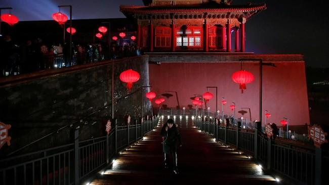 Tembok-tembok di kawasan Kota Terlarang juga dihiasi oleh sorotan cahaya berupa karakter khas China, seperti babi yang menjadi lambang tahun baru ini. (REUTERS/Jason Lee)
