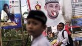 Hal yang rutin terjadi setiap lima tahun di mana alat peraga kampanye menjamur jelang Pemilu. Tampak seorang pelajar melintas di depan spanduk calon legislatif di Lhoksumawe, Aceh yang dibakar orang tak bertanggungjawab. (ANTARA FOTO/Rahmad)