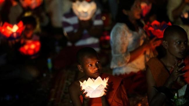 Yang menarik adalah saat malam tiba. Para biksu—masyarakat juga bisa ikut berpartisipasi—mengenakan busana kebesarannya dan membawa mangkuk berisi lilin. (REUTERS/Samrang Pring)