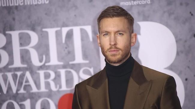 Calvin Harris terlihat mengagumkan dengan potongan jas dan celana yang pas badan. Dia juga termasuk berani dengan memakai warnacopper.(Photo by Joel C Ryan/Invision/AP)