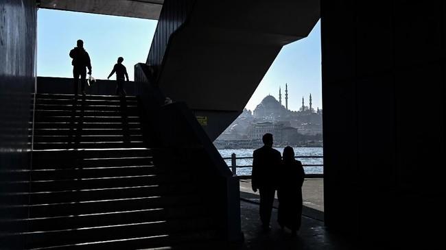 Pada suatu hari yang cerah, orang-orang berjalan di jembatan Galata di depan masjid Suleymaniye di distrik Karakoy di Istanbul. (Photo by OZAN KOSE / AFP)