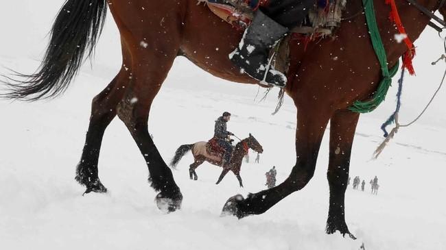 Pemuda Afghanistan menunggangi kuda di atas tanah yang tertutupi salju di luar kota Kabul. (REUTERS/Omar Sobhani)
