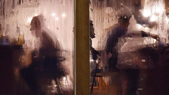 Pengunjung yang sedang menikmati makan malam di suatu restoran di Beijing, China, terlihat dari balik jendela yang beruap. (Photo by Greg Baker / AFP)