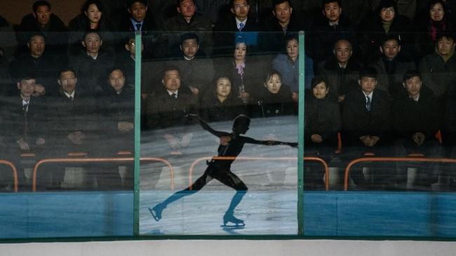 Bayangan seorang atlet seluncur es tercermin di suatu panel kaca, ketika para penonton menyaksikan Festival Seluncur Es Paektusan ke-26 di Pyongyang, Korea Utara. Festival ini merupakan rangkaian acara perayaan ulang tahun mendiang mantan pemimpin Korea Utara, Kim Jong Il. (Photo by Ed JONES / AFP)