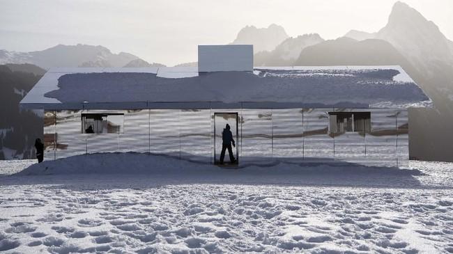 Rumah dua lantai yang dinamakan Mirage itu terlihat indah karena susunan kaca memantulkan panorama pegunungan yang sedang membeku di sekitarnya. (Anthony Anex/Keystone via AP)