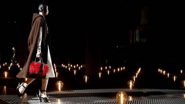 Arenacatwalk berhias lampu kuning temaram yang dipasang berhimpitan menjadi tempat para model berlenggak-lenggok dalam balutan Prada yang lembut.(REUTERS/Alessandro Garofalo)