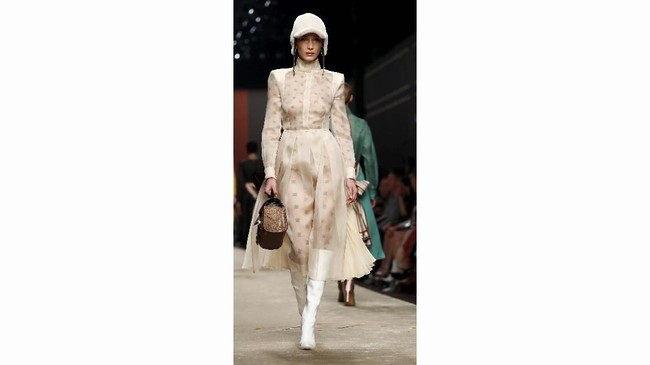 Lagerfeld juga bermain dengan konsep layer dan penggunaan bahan transparan serta kulit yang 'dilubangi' dengan laser. Warna-warnanya cukup aman meski ia menyematkan warna kuning yang mencolok. (REUTERS/Alessandro Garofalo)