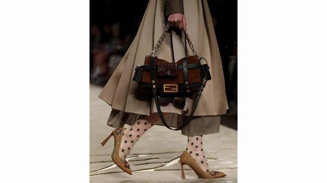 Tak cuma itu, penampilan para model pun dilengkapi dengan ragam tas Fendi yang tersohor, namun dengan sentuhan anyar. Sebagai contoh, tas Peekaboo berlubang atau Baguette berwarna pastel. (REUTERS/Alessandro Garofalo)