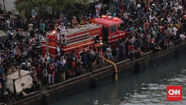 Warga menyaksikan kebakaran di Pelabuhan Nizam Zachman Muara Baru, Jakarta. Sabtu (23/2). (CNN Indonesia/Adhi Wicaksono)