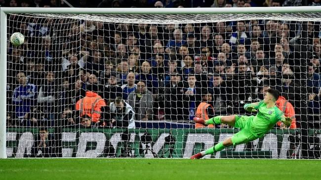 Namun Kepa Arrizabalaga gagal memperpanjang napas Chelsea. Ia terkecoh oleh tendangan Raheem Sterling. Chelsea kalah 3-4 dalam duel adu penalti. (REUTERS/Rebecca Naden)