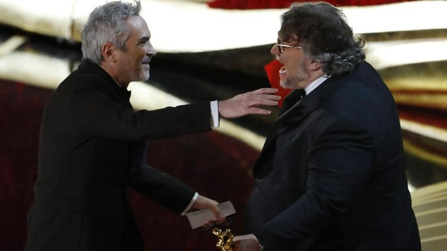Sutradara asal Meksiko, Guillermo del Toro (kanan) tak dapat menahan kegembiraan kala sahabatnya, Alfonso Cuaron membawa pulang piala Oscar untuk Best Director berkat 'Roma'. (REUTERS/Mike Blake)