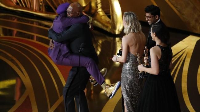 Sineas Spike Lee tak dapat menahan kegembiraannya berhasil membawa pulang piala Oscar untuk pertama kalinya usai 30 tahun berkarier lewat kategori Best Adapted Screenplay untuk 'BLACKkKLANSMAN'. Lee memeluk Samuel L Jackson begitu tiba di panggung Oscar. (REUTERS/Mike Blake)