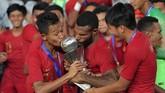 Pemain Timnas U-22 Sani Riski Fauzi (kiri) bersama Marinus Wanewar (tengah) mencium Piala AFF U-22 seusai penganugerahan piala di Stadion Nasional Olimpiade Phnom Penh, Kamboja, Selasa (26/2/2019). Indonesia menjadi juara setelah mengalahkan Thailand di babak final dengan skor 2-1. ANTARA FOTO/Nyoman Budhiana/nz