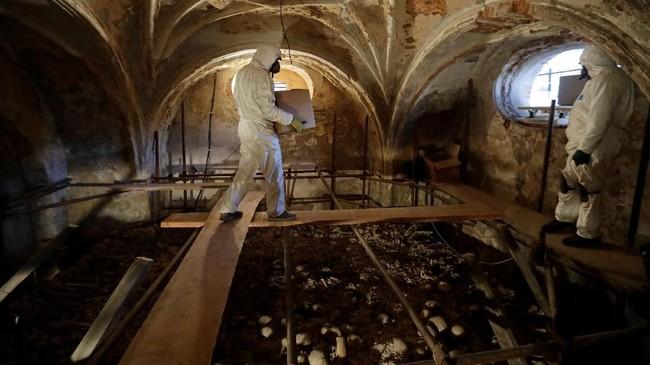 Seorang ahli restorasi mengangkat sebuah kotak berisi tulang-belulang dari zaman pertengahan. (REUTERS/David W Cerny)