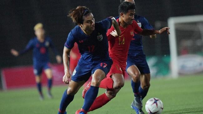 Pemain Timnas U-22 Asnawi Mangkualam Bahar (tengah) berebut bola dengan pemain Thailand Sakunchai Saengthopho (kiri). (ANTARA FOTO/Nyoman Budhiana/ama)