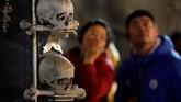 Pengunjung mengamati tengkorak kepala manusia yang terpajang di dalam gereja. (REUTERS/David W Cerny)