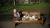 Pria duduk santai di bangku Taman St James, London, Inggris. (REUTERS/Henry Nicholls)