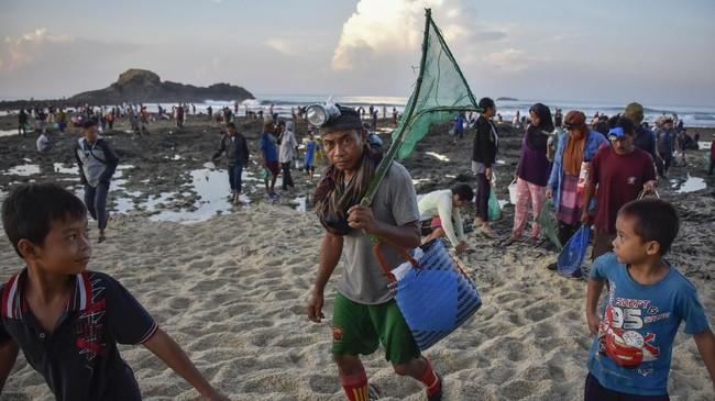 Sejumlah warga meninggalkan pantai usai menangkap nyalepada Festival Pesona Bau Nyale 2019 di pantai Seger Kawasan Ekonomi Khusus (KEK) Mandalika. Cacing yang didapat juga akan dikonsumsi. (ANTARA FOTO/Ahmad Subaidi)