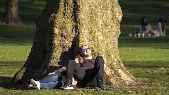 Sepasang kekasih menikmati hangatnya matahari musim semi di Taman St James, London, Inggris. (Niklas HALLE'N / AFP)