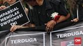 Massa aksi mengenakan pakaian serba hitam, payung hitam, dan berdiri menghadap Istana Merdeka sambil membentangkan spanduk menuntut pemerintah segera menuntaskan kasus-kasus pelanggaran HAM dan penolakan kembalinya militer untuk menduduki jabatan sipil. (CNN Indonesia/Adhi Wicaksono)