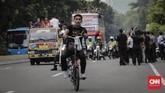 Seorang suporter Timnas Indonesia mengikuti arak-arakan dengan menggunakan sepeda. (CNN Indonesia/Adhi Wicaksono)