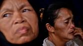 Dua orang wanita menanti kabar anggota keluarganya yang tertimbun longsor di lokasi Pertambangan Emas Tanpa Izin (PETI) Desa Bakan, Kecamatan Lolayan, Kabupaten Bolaang Mongondouw, Sulawesi Utara. (ANTARA FOTO/Adwit B Pramono/ama).