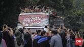 Sejumlah karyawan kantor yang terletak di Jl. Jenderal Sudirman ikut mengabadikan arak-arakan Timnas Indonesia U-22. (CNN Indonesia/Adhi Wicaksono)