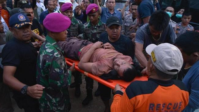 Petugas menggotong seorang penambang yang selamat dari lokasi Pertambangan Emas Tanpa Izin (PETI) Desa Bakan, Kecamatan Lolayan, Kabupaten Bolaang Mongondouw, Sulawesi Utara, Rabu (27/2). (ANTARA FOTO/Adwit B Pramono/ama).