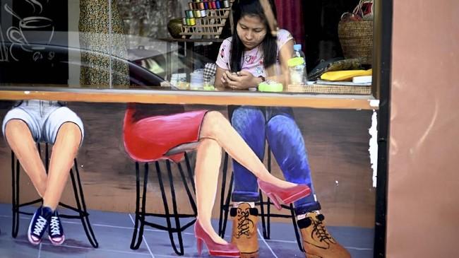 Seorang perempuan menggunakan telepon genggam sembari menunggu konsumen di toko miliknya yang terletak di suatu pasar di Yangon. (Photo by JEWEL SAMAD / AFP)