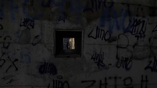Di zona buffer PBB, bayangan seorang tetua yang sedang melintas terlihat lewat sebuah bingkai. Zona itu membelah ibu kota Siprus, Nicosia, ke dalam beberapa bagian. (AP Photo/Petros Karadjias)