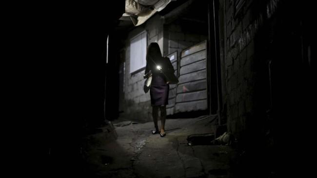 Janice Sarad, 22, yang bekerja untuk suatu bank, meninggalkan area tempat tinggalnya di Antipolo City, Provinsi Rizal, Filipina, untuk pergi bekerja. Sarad meninggalkan rumahnya sekitar pukul 04.30-05.00 pagi hari agar tepat waktu sampai di kantor pukul 08.30 pagi. (REUTERS/Eloisa Lopez)