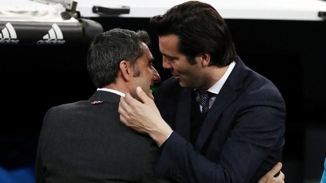 Pelatih Real Madrid Santiago Solari dan pelatih Barcelona Ernesto Valverde berpelukan sebelum laga di Santiago Bernabeu, Sabtu (2/3) malam waktu setempat. (REUTERS/Sergio Perez)